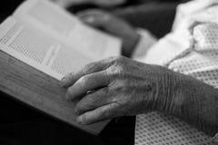 Libro de lectura del viejo hombre Ciérrese para arriba de manos arrugadas Imágenes de archivo libres de regalías