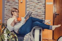 Libro de lectura envejecido medio de la mujer y café de consumición en casa imagen de archivo