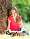 Libro de lectura feliz de la muchacha del estudiante Imagenes de archivo