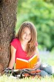 Libro de lectura feliz de la muchacha del estudiante Fotos de archivo libres de regalías