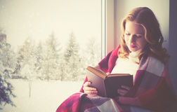 Libro de lectura feliz de la muchacha por la ventana en invierno Imágenes de archivo libres de regalías