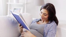 Libro de lectura feliz de la mujer embarazada en casa almacen de video