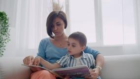 Libro de lectura feliz del hijo de la madre y del niño que ríe en cama Libro feliz de la tenencia de la lectura del hijo de la ma almacen de metraje de vídeo