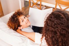 Libro de lectura feliz del muchacho del preadolescente que se sienta en el sofá Imágenes de archivo libres de regalías