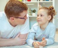 Libro de lectura feliz joven del padre con la hija linda en casa imagenes de archivo