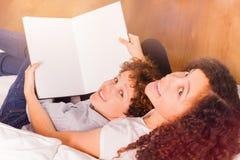 Libro de lectura feliz de los adolescentes junto en casa Imagen de archivo libre de regalías