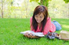 Libro de lectura feliz tailandés de la mujer en parque Foto de archivo libre de regalías