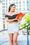 Libro de lectura femenino americano del estudiante universitario, estudiando en campus Fotografía de archivo libre de regalías