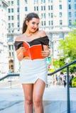 Libro de lectura femenino americano del estudiante universitario, estudiando en campus Foto de archivo libre de regalías