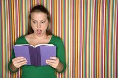 Libro de lectura femenino caucásico que hace la expresión. Fotografía de archivo