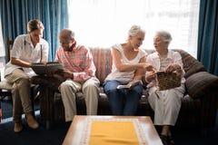 Libro de lectura femenino del doctor con el hombre mientras que mujeres mayores que hablan contra ventana Imagen de archivo libre de regalías