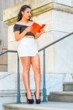 Libro de lectura femenino del estudiante universitario de Amercan, estudiando en campus Imagen de archivo