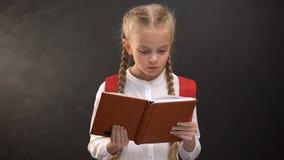 Libro de lectura femenino elegante del niño, pizarra en el fondo, sed para el conocimiento almacen de video