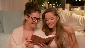 Libro de lectura femenino feliz de los amigos en casa almacen de metraje de vídeo
