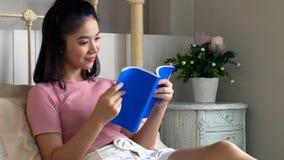 Libro de lectura femenino joven asiático en el colchón en dormitorio Imagen de archivo libre de regalías