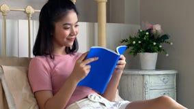 Libro de lectura femenino joven asiático en el colchón en dormitorio Foto de archivo