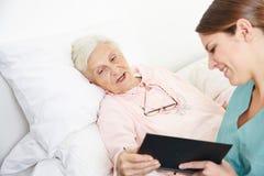 Libro de lectura geriátrico de la enfermera Imágenes de archivo libres de regalías