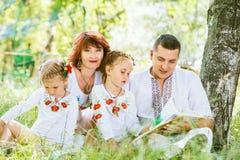 Libro de lectura hermoso de la familia junto en parque fotografía de archivo