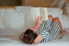 Libro de lectura hermoso de la mujer en la cama que se relaja Foto de archivo