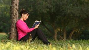 Libro de lectura hermoso de la mujer en la naturaleza almacen de metraje de vídeo