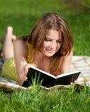 Libro de lectura hermoso de la mujer joven al aire libre Fotografía de archivo libre de regalías