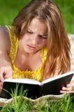 Libro de lectura hermoso de la mujer joven al aire libre Imagen de archivo libre de regalías