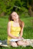 Libro de lectura hermoso de la mujer joven al aire libre Fotos de archivo