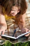 Libro de lectura hermoso de la mujer joven al aire libre Fotos de archivo libres de regalías