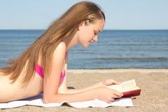 Libro de lectura hermoso del adolescente en la playa Imagen de archivo libre de regalías