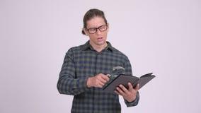 Libro de lectura hermoso del hombre del inconformista con la lupa almacen de metraje de vídeo