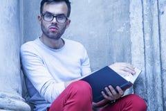Libro de lectura hermoso del hombre joven al aire libre contra fondo gris fotografía de archivo libre de regalías