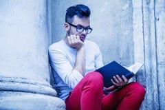 Libro de lectura hermoso del hombre joven al aire libre contra fondo gris fotografía de archivo