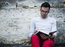 Libro de lectura hermoso del hombre joven al aire libre en el viejo europeo CIT fotos de archivo libres de regalías
