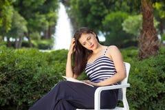 Libro de lectura hermoso joven de la señora en parque. Foto de archivo