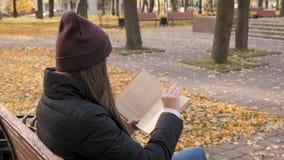 Libro de lectura hermoso joven de la muchacha en parque del otoño almacen de metraje de vídeo
