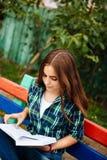 Libro de lectura hermoso de la muchacha al aire libre, con el espacio de la copia imágenes de archivo libres de regalías