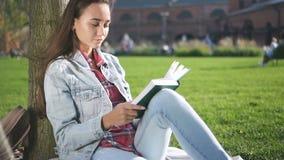Libro de lectura inspirado del estudiante universitario que se sienta en hierba del campus almacen de metraje de vídeo