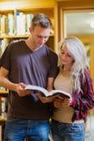 Libro de lectura joven de dos estudiantes en la biblioteca Foto de archivo libre de regalías