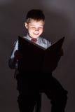 Libro de lectura joven del colegial en la oscuridad Fotos de archivo