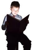 Libro de lectura joven del colegial en la oscuridad Fotografía de archivo