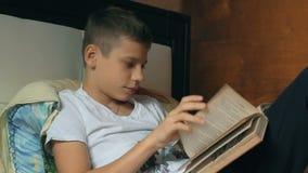 Libro de lectura joven del muchacho en el sofá Libro de lectura del niño Cabrito que hace la preparación almacen de metraje de vídeo