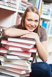 Libro de lectura joven sonriente de la mujer adulta en biblioteca Imagen de archivo libre de regalías
