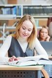 Libro de lectura joven sonriente de la mujer adulta en biblioteca Fotografía de archivo