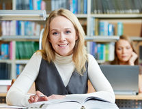 Libro de lectura joven sonriente de la mujer adulta en biblioteca Imagenes de archivo