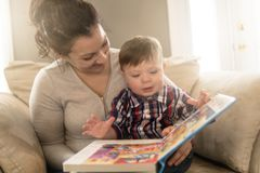 Libro de lectura de la madre con su niño en el sofá foto de archivo