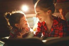 Libro de lectura de la madre y del niño en cama antes de ir a dormir fotos de archivo libres de regalías