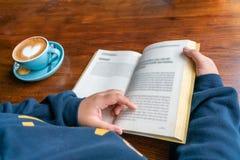 Libro de lectura de la mano de la mujer y café de consumición fotos de archivo libres de regalías