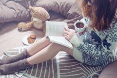 Libro de lectura de la muchacha en cama con los calcetines calientes que beben el café Imagenes de archivo