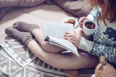 Libro de lectura de la muchacha en cama con los calcetines calientes que beben el café Imagen de archivo libre de regalías