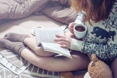 Libro de lectura de la muchacha en cama con los calcetines calientes que beben el café Fotografía de archivo